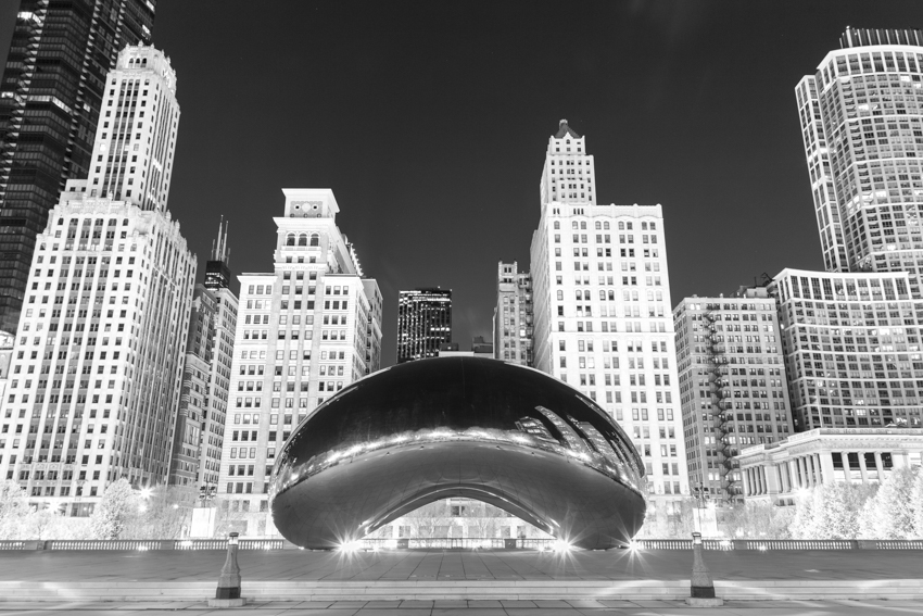 The Chicago Bean at night with skyscraper buildings in the background